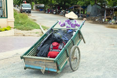 Wheelbarrow hand cart carrier porter wearing vietnamese hat, Vietnam Stock Photo