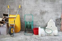 Wheelbarrow, hose and cartons Stock Photo