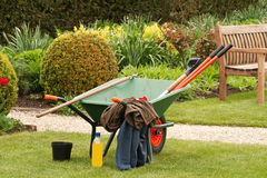 Wheelbarrow with jackets and bottle of drink Stock Images