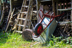 Wheelbarrow leaning overhead on a shed with messy stacked wood royalty free stock photography