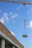 Wheelbarrow lifting by construction crane Stock Image