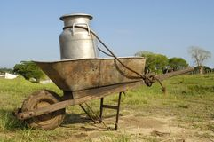 Wheelbarrow and milk churn Stock Image