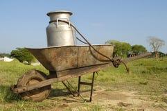 Wheelbarrow and milk churn Stock Image