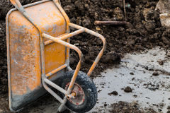 Wheelbarrow. Old yellow wheelbarrow with lime stains in construction work area, selective focus Stock Photo