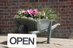 Wheelbarrow planted with flowers and open sign Royalty Free Stock Images