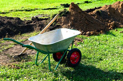 Wheelbarrow with rake Royalty Free Stock Image