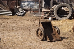 Wheelbarrow for removal of manure, rural courtyard. Royalty Free Stock Image