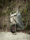 Wheelbarrow resting on a wall. Vertical. Royalty Free Stock Photo
