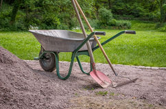 Wheelbarrow with a shovel and rake Royalty Free Stock Photography