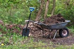 Wheelbarrow and spade. Metal wheelbarrow and space with blue handle Royalty Free Stock Photography
