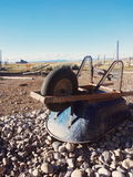 Wheelbarrow. At sunset. Desolate farm land with old vintage barn in background Royalty Free Stock Photography
