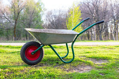 Wheelbarrow to work in the garden. Standing on a green grass 2 Royalty Free Stock Photos