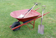 Wheelbarrow with Various Tools. A common red wheelbarrow sits on a lawn srrounded by gardening and landscaping equipment royalty free stock image