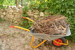 Wheelbarrow with waste wood Stock Images