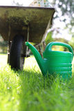 Wheelbarrow and watering can stock photography