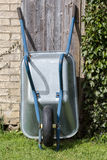 Wheelbarrow. Wheellbarow in garden at shed Royalty Free Stock Images