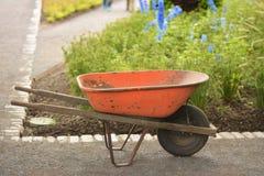Wheelbarrow for work in outdoor. Old rusty wheelbarrow cart in the garden.Colorful summer garden.Working in the garden Royalty Free Stock Photos