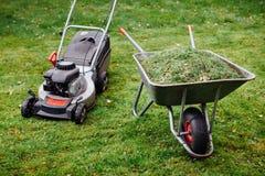Wheelbarrow z trawą i lawnmower na zielonym gazonie Zdjęcie Royalty Free