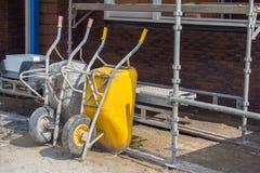 Wheelbarrows και υλικά σκαλωσιάς στο εργοτάξιο οικοδομής Στοκ εικόνες με δικαίωμα ελεύθερης χρήσης