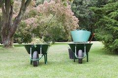 Wheelbarrows, buckets and gardening tools in mature formal garden Royalty Free Stock Photos