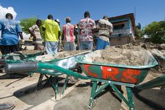 Wheelbarrows of Mud. September 29, 2008 - Locals in Gonaives, Haiti, receive pay from a humanitarian agency to begin cleaning up the mud left behind in the wake Stock Images