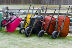Wheelbarrows resting against fence Royalty Free Stock Photo