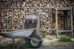 Wheelbarrows and wooden logs stored for winter on a country farm Stock Photo