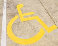 Wheelchair. Yellow wheelchair handicap road sign painted on a yellow pavement Stock Image