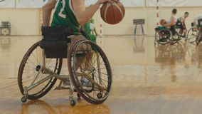 Wheelchair basketball player dribbling the ball quickly during training of disabled sportsmen. Close up Stock Image