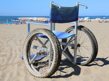 Wheelchair on the beach sand near the sea Stock Image