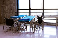 Wheelchair and bed at hospital area.  stock photos