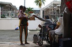 Wheelchair beggar giving bread pellets to pregnant woman cuddling child as gift during Christmas time. San Pablo City, Laguna, Philippines - December 17, 2016 Stock Photos