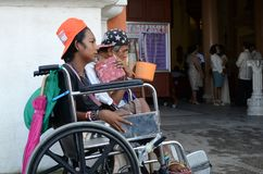 Wheelchair beggar holding dipper seeking alms at church gate portal ruins. San Pablo City, Laguna, Philippines - December 17, 2016: wheelchair beggar holding royalty free stock photography