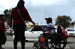 Wheelchair beggar receiving Christmas gift alms at church yard. San Pablo City, Laguna, Philippines - December 21, 2016: wheelchair beggar receiving Christmas Stock Image