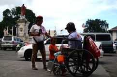Wheelchair beggar receiving Christmas gift alms at church yard. San Pablo City, Laguna, Philippines - December 21, 2016: wheelchair beggar receiving Christmas stock photo