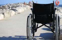 Wheelchair from behind near the shore of the sea Royalty Free Stock Photos