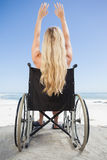 Wheelchair bound blonde sitting on the beach with arms up Stock Image