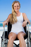 Wheelchair bound blonde sitting on the beach smiling at camera Royalty Free Stock Photo