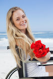 Wheelchair bound blonde smiling at the camera on the beach holding roses Royalty Free Stock Photography