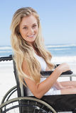 Wheelchair bound blonde smiling at the camera on the beach Royalty Free Stock Images