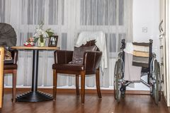 Wheelchair close to chair in a retirement home.  Stock Photography