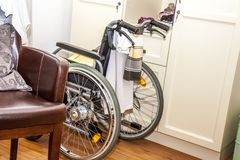 Wheelchair close to chair in a retirement home.  Stock Photos