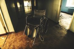 A derelict wheelchair inside an abandoned hospital. Wheelchair in the corridor of an abandoned hospital stock images