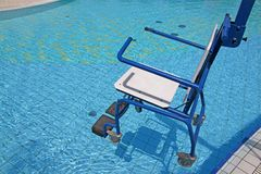 Wheelchair for the disabled in swimming pool stock images