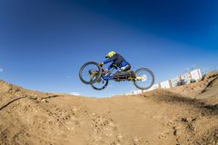 Wheelchair Downhill Rider jumping. Dirt bike weelchair. Disabled Sports. Wheelchair Downhill Rider at Mountain. Dirt bike weelchair . Disabled Sports royalty free stock photos