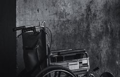 Wheelchair folded beside the wall. Sad news at the hospital concept. Depression with aging society. Lonely empty wheelchair. Medical equipment for service royalty free stock photography
