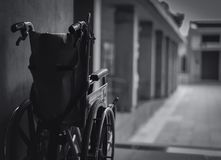 Wheelchair folded beside the wall. Sad news at the hospital concept. Depression with aging society. Lonely empty wheelchair. Medical equipment for service stock photography