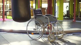 A wheelchair is in the gym.The concept of sports injury. Empty wheelchair is standing in the gym.Next to hanging punching bag.The concept of sports injury.Sun stock video footage