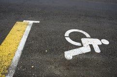 Wheelchair Handicap Sign on asphalt road street background. Wheelchair Handicap Sign on dark asphalt road street background- handicap parking place Stock Images