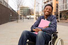Wheelchair. Happy young disabled man in a wheelchair holding folders Royalty Free Stock Photo